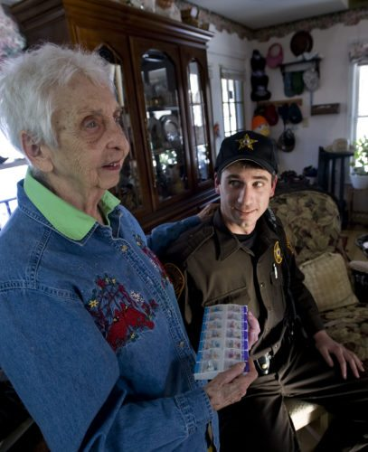 Mona Bowden, 88, left, holds her pill box while she chats with Warren County Sheriff's deputy Jesse Henry inside her home near Shenandoah River Estates in Front Royal on Wednesday.   Rich Cooley/Daily