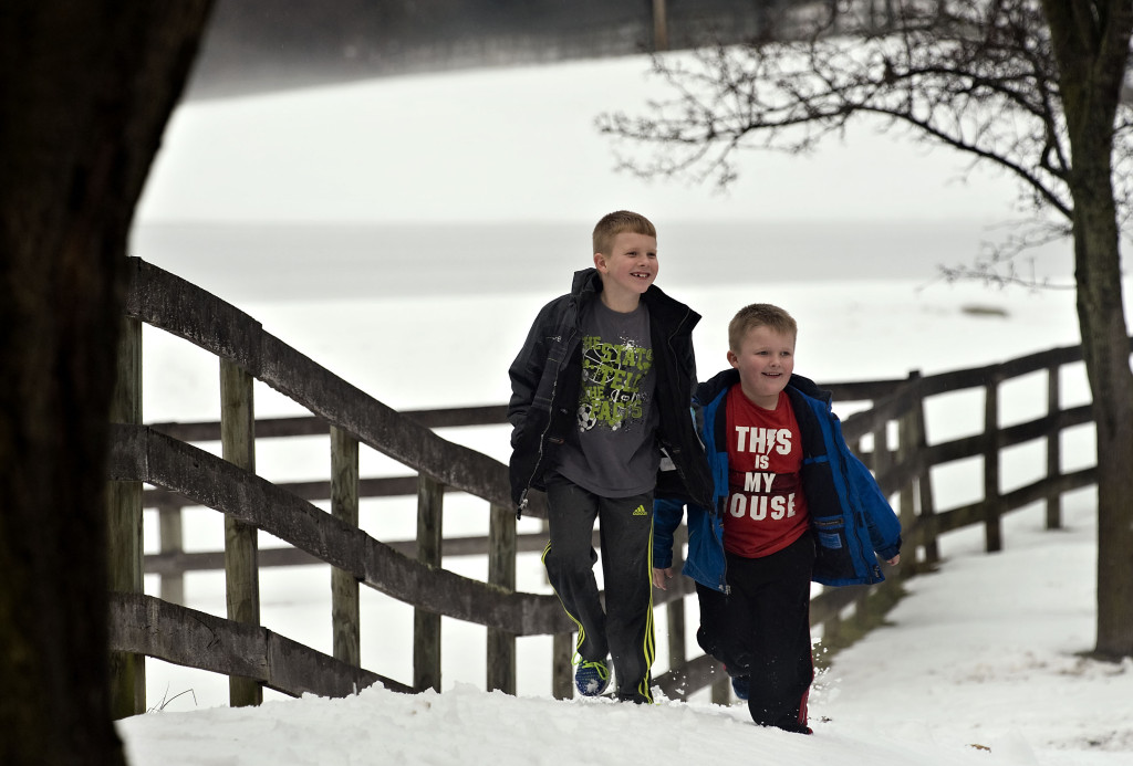 Xander Haley, 7, left, and his brother Austin, 6, walk through the snow along a fence after getting off the bus along Sandy Hook Road in Strasburg on Monday. Shenandoah County Public Schools restarted Monday after a week off from the snow and professional days.  Rich Cooley/Daily