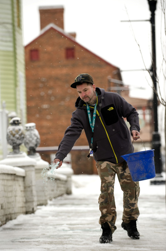 Stan Wolfrey, of Baker, West Virginia, tosses a salt substitute onto the sidewalk outside Gents Barbershop on West King Street in Strasburg on  Monday morning. Wolfrey was clearing the sidewalks where he works as a barber. Rich Cooley/Daily