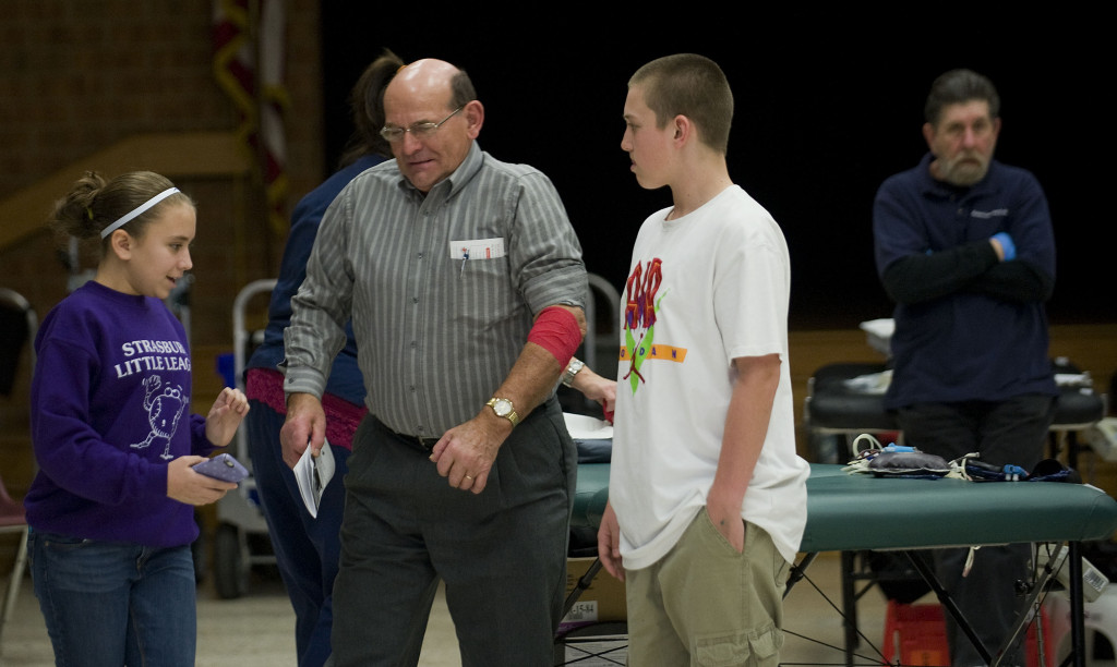 Signal Knob Middle School FFA students Chloe Copeland, left, and Cameron Rutz, right, both 12, escort Bob Coverstone, of Fort Valley, after he donated blood at the middle school on Monday afternoon. The school's FFA chapter sponsored the blood drive for the American Red Cross as part of its FFA Week activities.  Rich Cooley/Daily