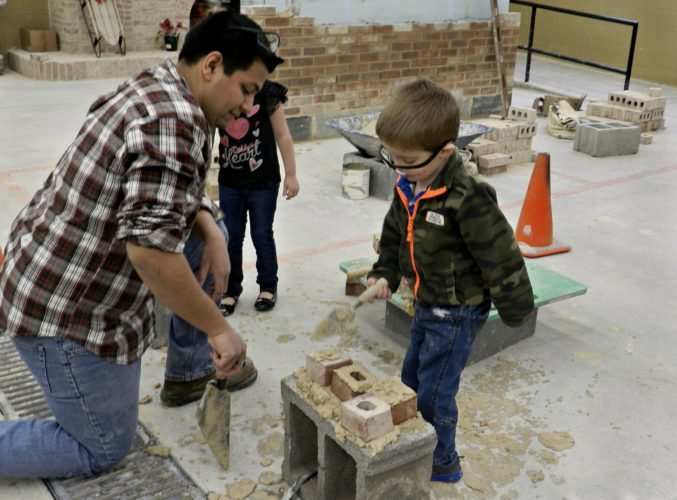 Graciel Tapia, 18, a second-year student at Triplett Tech, shows preschooler Benjamin Myers, 4, of Edinburg, how to lay brick down with mortar. Kaley Toy/Daily