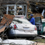 Timothy Williams looks over a car in front of his destroyed mobile home as he walks through debris left by a deadly storm that  on  Wednesday.  Williams was in the car that he is standing next to when a storm hit. AP Photo/Steve Helber
