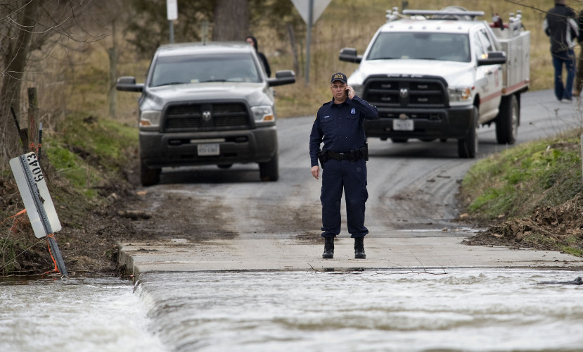 Virginia state police Sgt. Phil King talks on his cell phone while watching water cross the Artz Road bridge Thursday afternoon east of Woodstock. Melba Jo Rice, 78, of Woodstock was killed as her vehicle was swept off the bridge in high water Thursday morning. Her body and car were recovered late Thursday afternoon. Rich Cooley/Daily