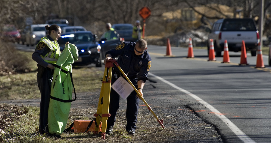 State troopers P.M. Neff, left, and D.R. Gray, right, pack up their equipment after doing reconstruction work on a crash on Remount Road that occurred early Monday morning. A Warren County woman died in the crash. Rich Cooley/Daily