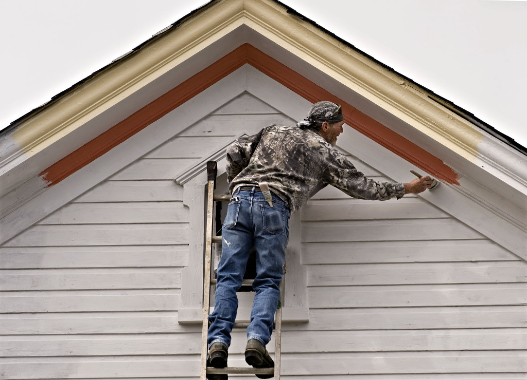 Pat Adams of Front Royal paints the trim on this two story home at Blue Ridge Avenue and Stonewall Drive in Front Royal on Monday.  Rich Cooley/Daily