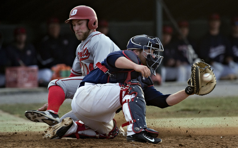 Dickinson's Ryan Dolan beats a throw to home plate as Shenandoah University's catcher Dan Cameron waits for the ball during sixth inning action Monday evening at Bridgeforth Field.   Rich Cooley/Daily
