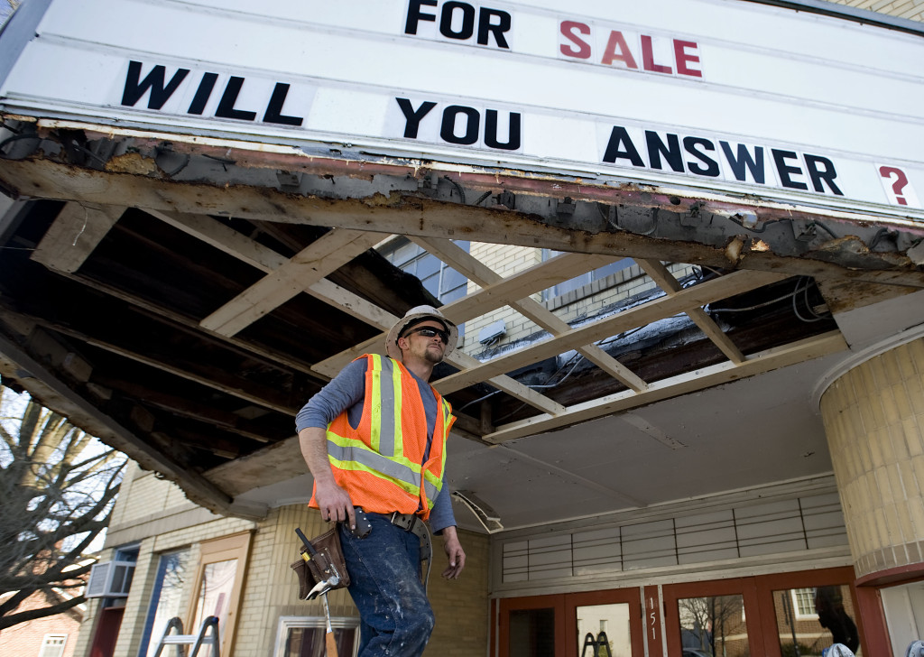 Ryan Silvious, a construction foreman for Team Craft Roofing of Woodstock, inspects progress on the reconstruction of the marquee of the former Home Theater in Strasburg on Tuesday.  A crew is making repairs this week to make it structurally sound.  Rich Cooley/Daily