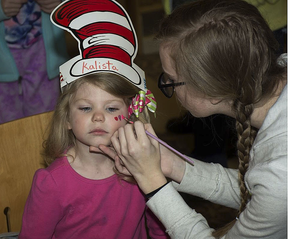 Jessica Pepper, a student at Shenandoah Valley Academy, paints Kalista Alexander's face during the New Market Area Library's celebration of Dr. Seuss' birthday.