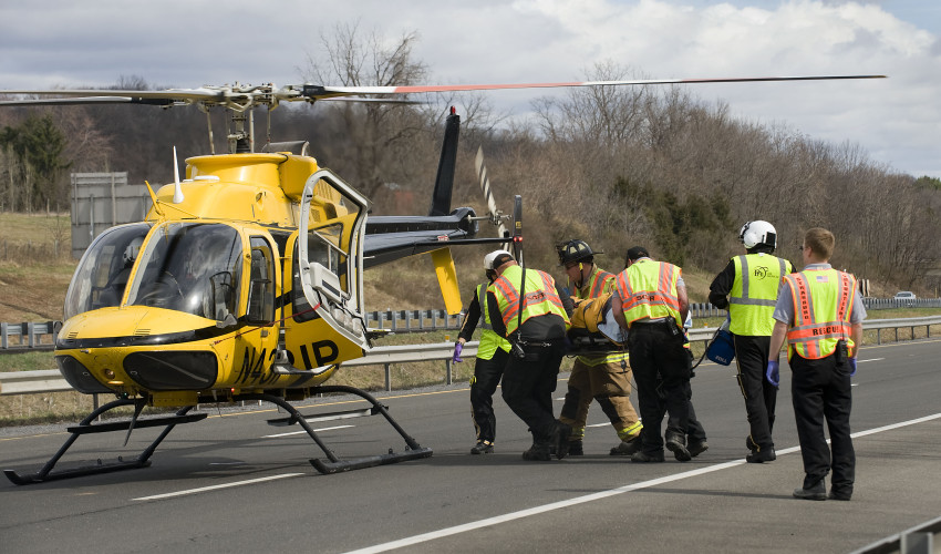 Fire and rescue personnel load the driver of an overturned  tractor trailer into a medical helicopter on Interstate 81 northbound just north of Toms Brook on Friday morning. Read story on  A6. Rich Cooley/Daily