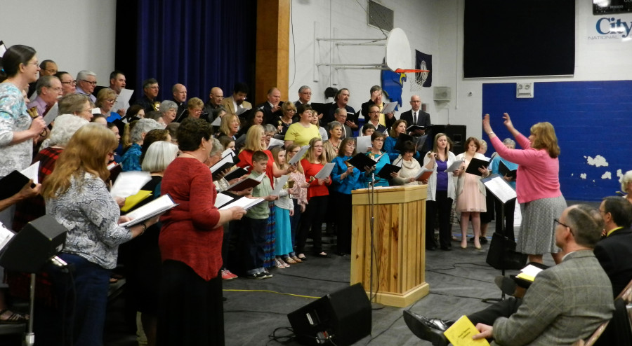 Libby Rocco, Family Promise of Shenandoah County board member, directs a chorus of singers from 17 churches during the affiliate's grand opening celebration at Central High School's gymnasium on Sunday. Rachel Mahoney/Daily