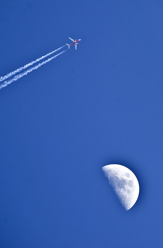 A jet flies in the evening sky at dusk as the moon sits below in this view near Woodstock.  Rich Cooley/Daily