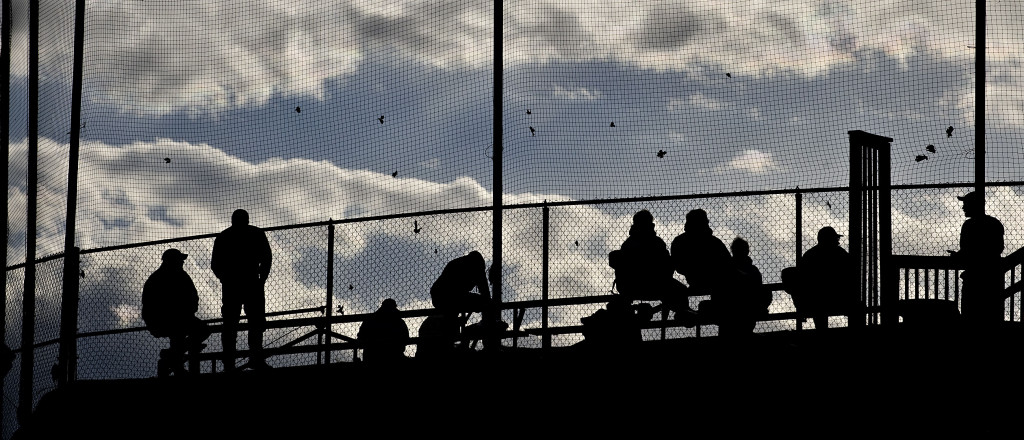 Baseball fans are in silhouette against the evening sky as they sit in the stands at Central High School in Woodstock recently.   Rich Cooley/Daily