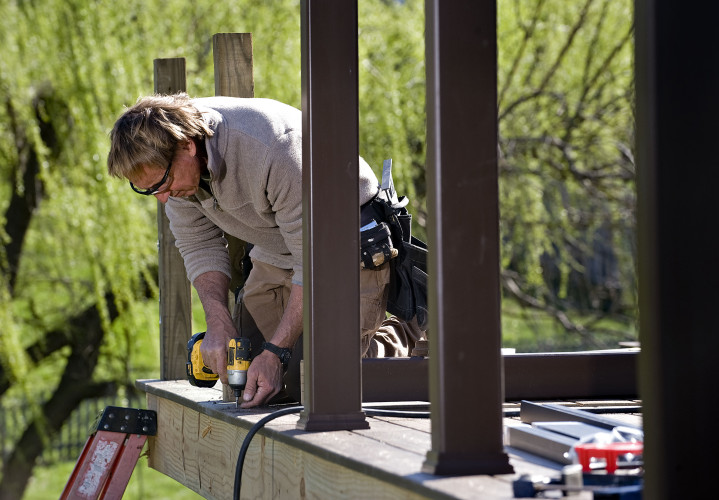 Dan Weir, owner of Dan's Decks, builds this Trex composite deck in the back of this home in Winchester. Rich Cooley/Daily