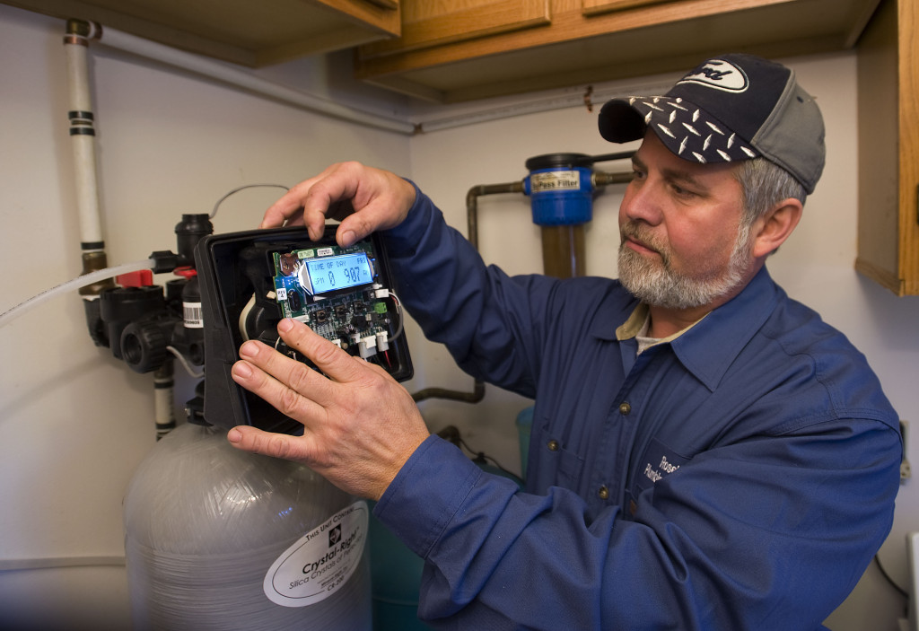 Mike Rose, co-owner of Rose's Plumbing, checks a water softener he installed  in a Toms Brook home recently. A water softener gives softer skin and hair  and  takes the minerals out of water  - including the calcium the causes build-up in hot water heaters. Rich Cooley/Daily