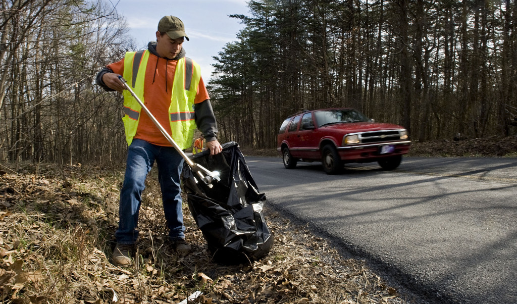 Northwestern Regional Adult Detention Center inmate David Shamer, of Martinsburg, picks up trash along Reynolds Road near the West Virginia line in western Frederick County. Rich Cooley/Daily