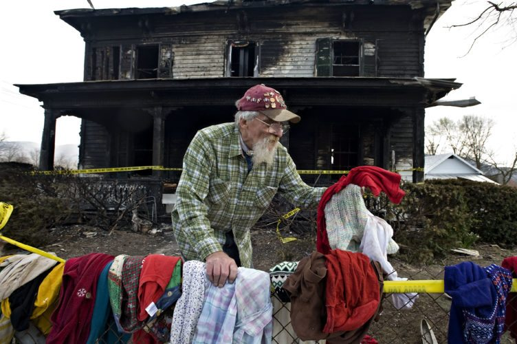 Daryl Hulvey, 68, places some of his wife's clothing that was salvaged from a Wednesday fire on the chain link fence outside his home along Old Valley Pike, north of Mount Jackson on Friday.  Rich Cooley/Daily