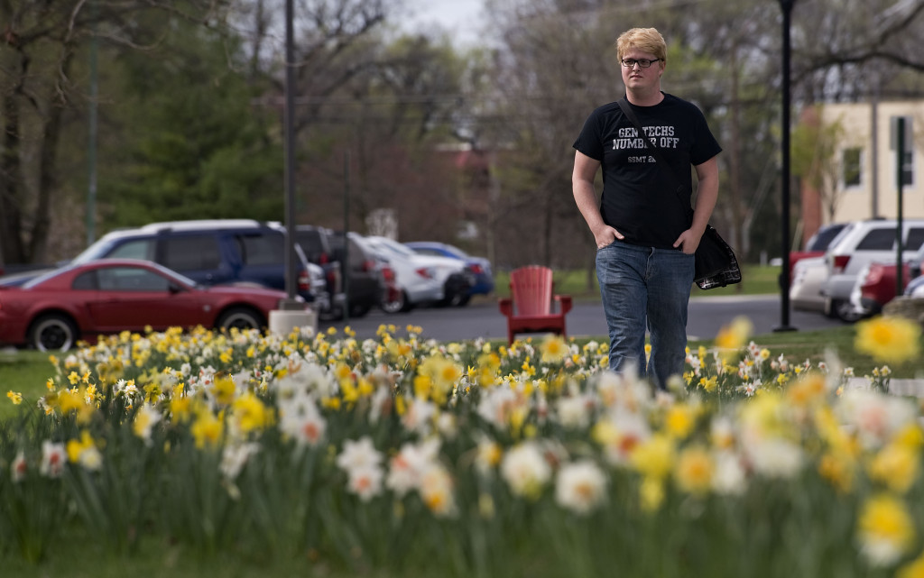Tony Matteson, 20, a Shenandoah University sophomore from Waynesboro, walks along this pathway lined with daffodils on the university's  campus recently. Rich Cooley/Daily