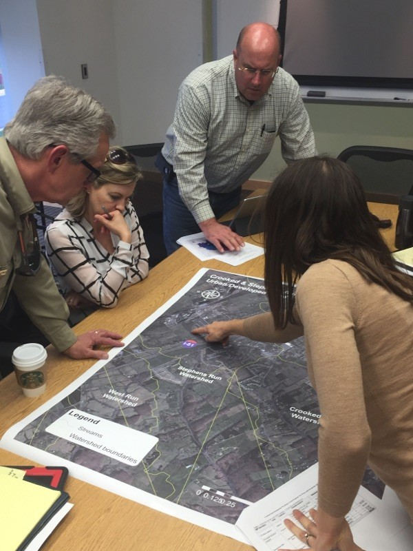 Nesha McRae, right, development coordinator for the Virginia Department of Environmental Quality's Valley Regional Office, points out possible locations for pet waste disposal units in residential areas near Stephens City at a residential working group meeting at Lord Fairfax Community College.  Rachel Mahoney/Daily