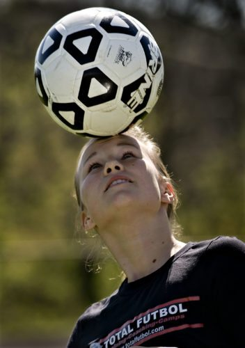 Strasburg sophomore Aileen Guthrie, 15,  performs a soccer ball trick outside Strasburg High School recently. Guthrie and Stonewall Jackson's Virginia Biller went to Hungary and Austria to play soccer for the state Olympic Development Team team.  Rich Cooley/Daily
