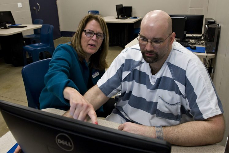 Kathryn Hamman, left, adult education instructor from Lord Fairfax Community College, sits beside Rappahannock-Shenandoah-Warren Regional Jail inmate Joseph Michael, 38, of Mount Jackson. Michael is the first inmate at the facility to earn a GED.  Rich Cooley/Daily