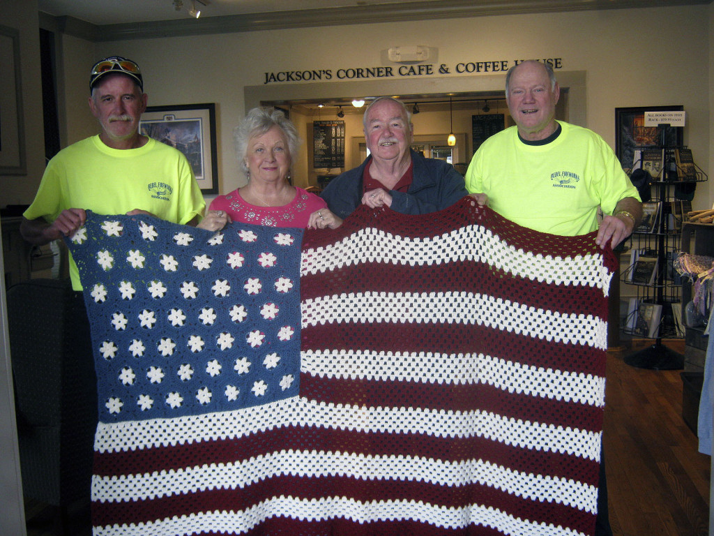 Bryan Rinker, left, and Ken Shomo, right, both of the Rebel Fireworks Association, present an American flag afghan made by Evelyn Faulkner of Warrenton, to Mr. and Mrs. Ed Blosser of Luray, center.  The flag was the prize in a fundraiser the association held to pay for this year's Independence Day fireworks display on July 3 at the New Market Community Park. The group plans to raffle a second afghan of a replica of the 1776 flag. Tickets go on sale today. Courtesy photo