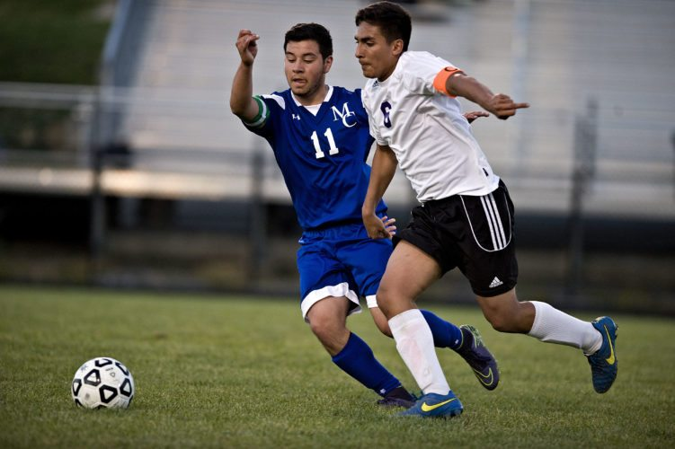 Madison County's Alejandro Tenorio, left, and Strasburg's Noe Medrano chase down the ball during the first half of their soccer match Friday night in Strasburg. Rich Cooley/Daily