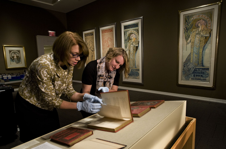 The Museum of the Shenandoah Valley will open a display of artwork by Alphonse Mucha today. Here, Nancy M. Huth, museum deputy director, arts and education, left, and  Kyle Briner, museum registrar and collections manager, look through a series of books featuring Mucha's artwork. Rich Cooley/Daily