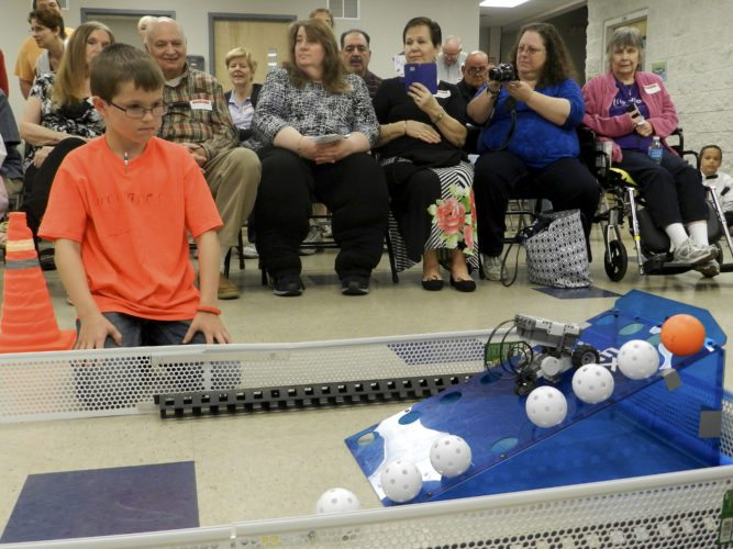 Buzzy Johnson, a third grader at Front Royal Christian School, watches his team's Lego robot score points at a robotics competition on Thursday. Rich Cooley/Daily