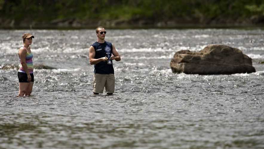 Ashley Ardinger, 23, left, and Wayne Wilson, 24, right, both of Harrisonburg, wade in the North Fork of the Shenandoah River near Camp Lupton east of Woodstock while fishing recently. Rich Cooley/Daily