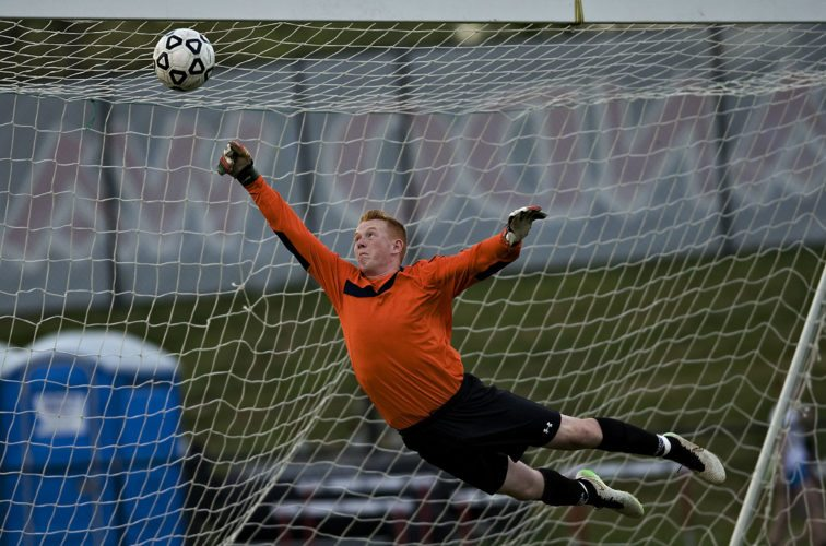 Sherando's goal keeper Brandon Teets manages to deflect a goal attempt during the first half of Monday night's soccer game against Handley. Rich Cooley/Daily