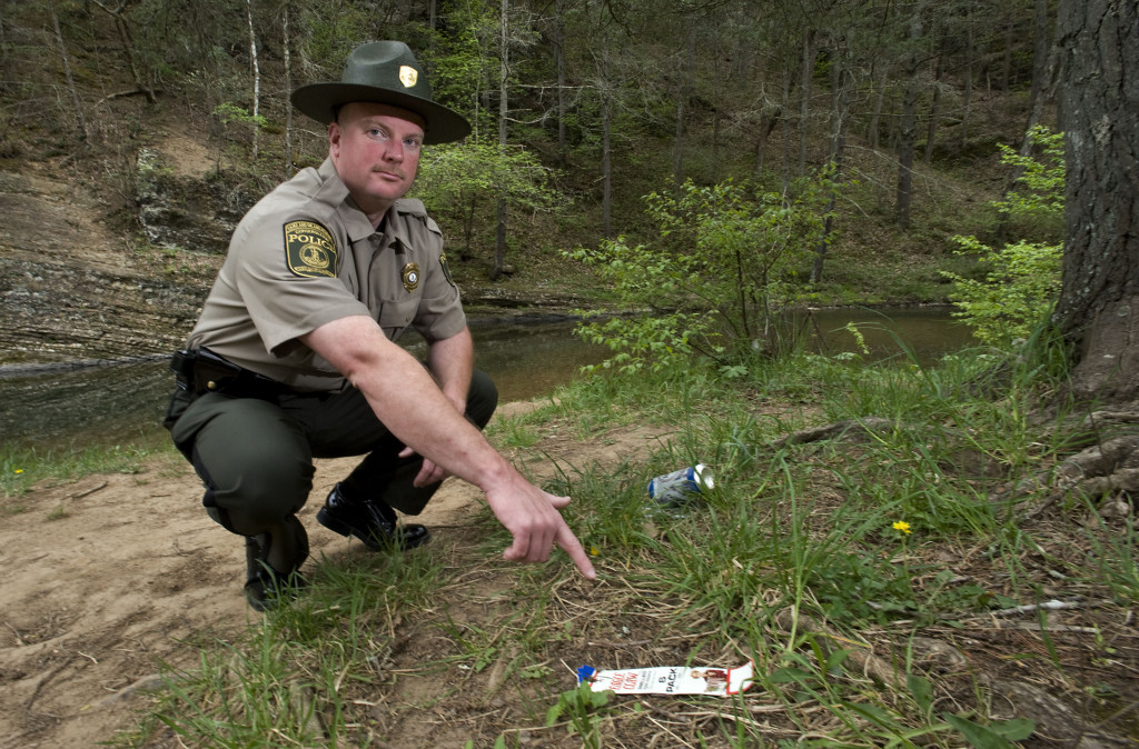 Owen Heine, a state conservation police officer, points to trash along Stony Creek near Columbia Furnace. Heine is  coordinating a spring cleanup effort scheduled for Saturday to pick up trash that is being left on private land along the banks of Mill and Stony Creeks.  Rich Cooley/Daily
