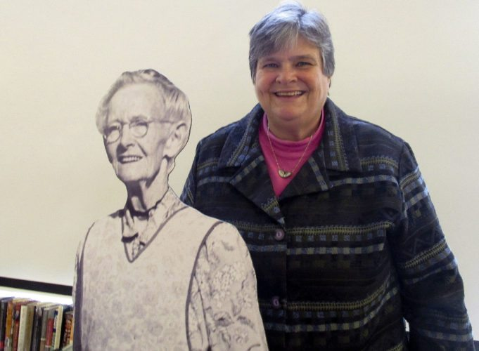 "Nancy Sorrells poses for a photo with a cut-out of folk artist Anna Mary Robertson Moses, aka, ""Grandma Moses,"" at a library program recently.  ​Photo courtesy Karen Whetzel"