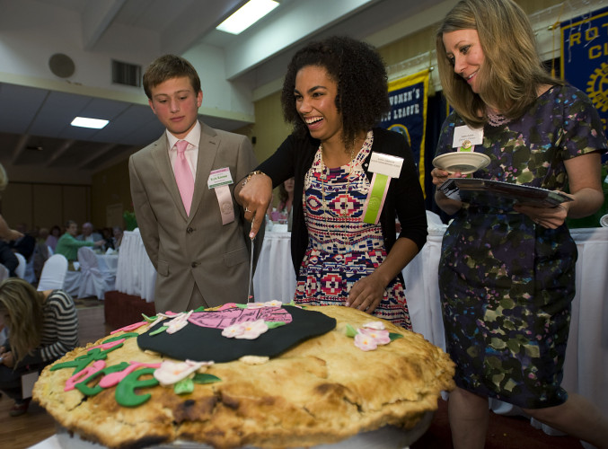 Queen Shenandoah designate LXXXIX Ahna Cameron prepares to slice he giant apple pieduring the Queen's Dinner held Thursday night at the Best Western Lee-Jackson in Winchester. At left is her escort Kyle Kremer, 16, of Winchester and at right is Anne Lewis who assisted in the ceremony.  Rich Cooley/Daily
