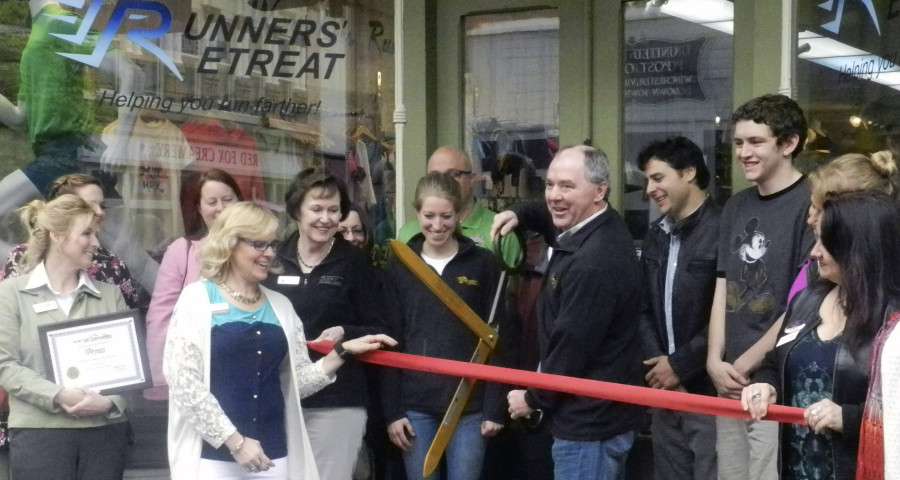 Runners' Retreat owner Mark Stickley uses a large pair of scissors to cut a ribbon in front of his Winchester store. Stickley won a $40,000 store makeover and welcomed customers in to see the changes on Friday.  Nathan Budryk/Daily