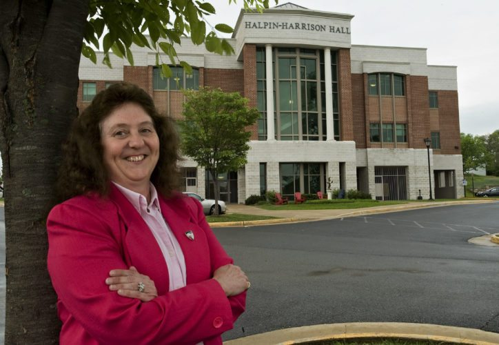 Mary Dyke, 53, of Winchester stands outside Halpin-Harrison Hall at Shenandoah University's Harry F. Byrd, Jr. School of Business on Monday. Dyke, a business major, will graduate Saturday from the university and will start her master's degree program in a few weeks.  Rich Cooley/Daily