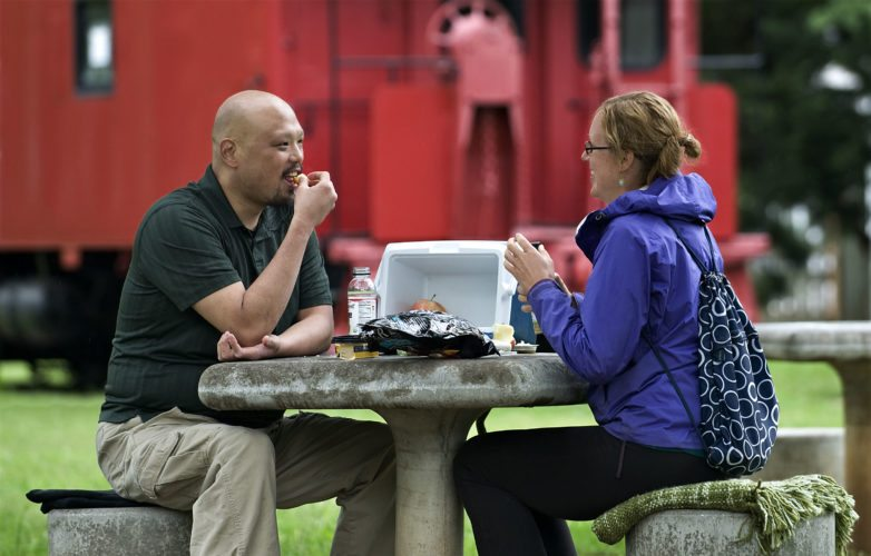 Paul Harada, left, and Ruby Mitchell, both of Fairfax, share a picnic lunch outside the Front Royal-Warren County Visitors Center on East Main Street during an afternoon drizzle Tuesday afternoon. They were visiting Skyline Caverns for the day.  Rich Cooley/Daily