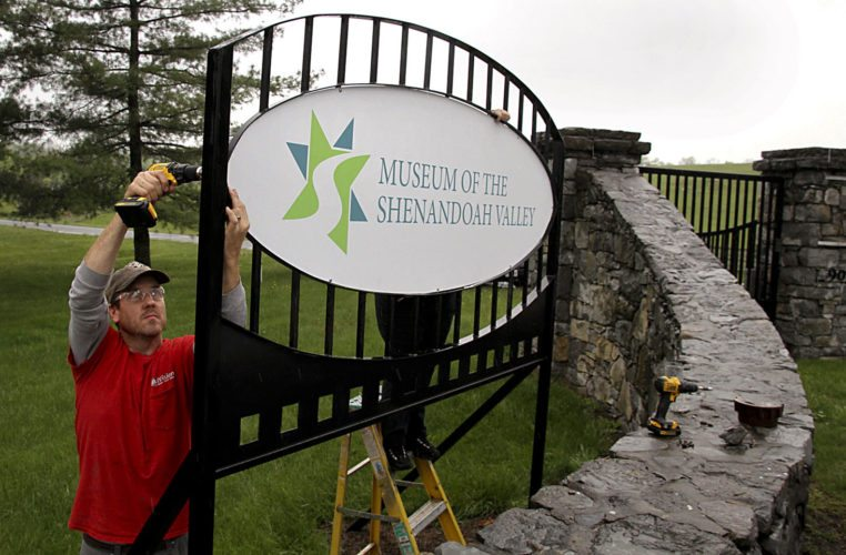 Howard Baker, left, and Carla Leen of AdVision Sign Company install one of two new Museum of the Shenandoah Valley signs at the Amherst Street entrance bearing the museum's new logo. Photo courtesy of MSV/Rick Foster