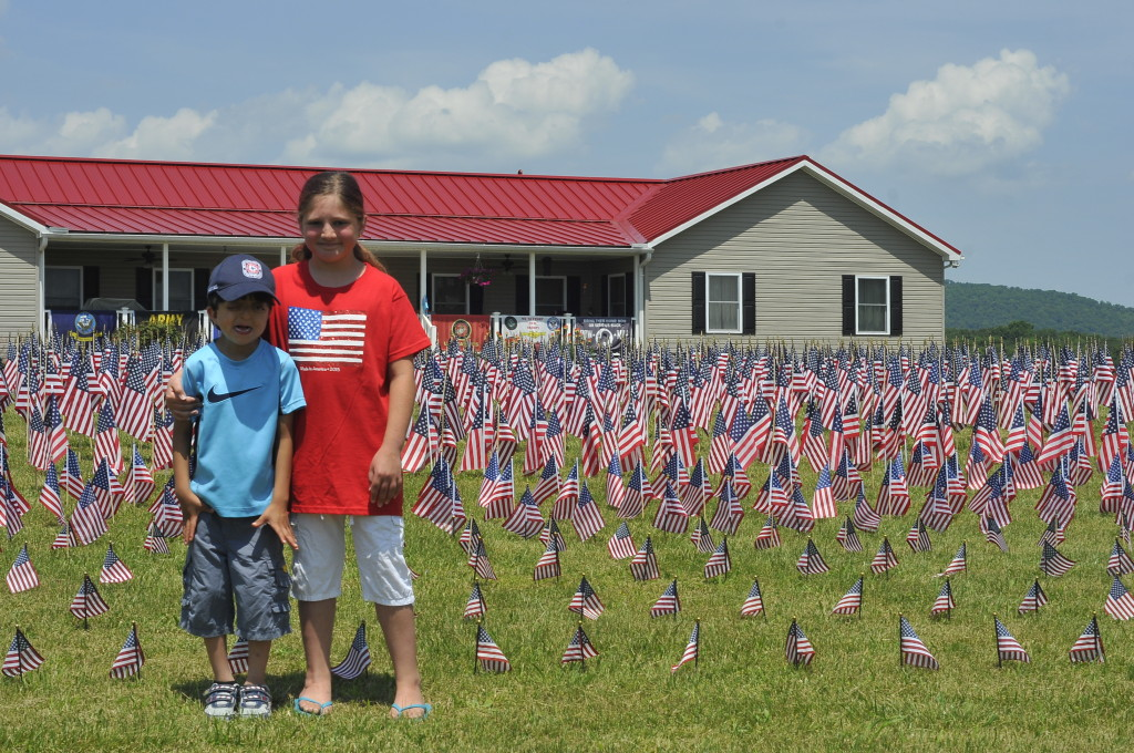 "Pamela and Gregory ""Junior"" Long stand amid a sea of American flags at their family's home in Strasburg.  This year the Longs planted more than 2,000 flags and 120 crosses for their Memorial Day commemoration.  Jake Zuckerman/Daily"