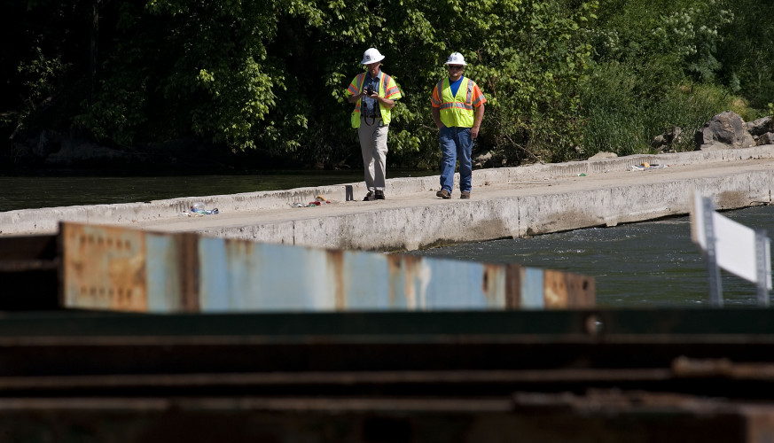 Ken Slack, Virginia Department of Transportation communications specialist, left, and bridge inspector Donnie Cummins walk along the Morgan Ford Bridge on Tuesday while piles of steel rest along the banks of the Shenandoah River. Contractors are preparing to use the steel to build a cofferdam and begin construction of the new bridge.     Rich Cooley/Daily