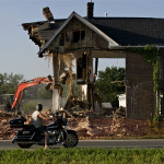 Gene Hamman, director of operations for FD Neal Construction Ltd., of Woodstock, demolishes an early 1900s house beside Rockingham Co-op in Strasburg on Wednesday evening, while Roland Palmer, of Strasburg, watches from his motorcycle. Demolition of the house, which is also owned by the Harrisonburg-based business, will allow the retail business to upgrade its entrance and pave the parking lot. The new store is also adding a 5,000-square-foot warehouse and a 5,500-square-foot Ace Hardware store. The upgrades are targeted to be completed by Sept. 1.  Rich Cooley/Daily
