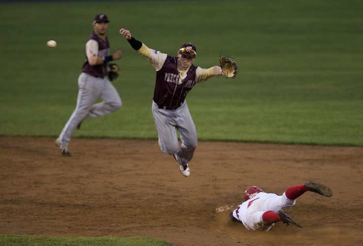 Front Royal Cardinals Kevin Williams Jr. slides head first safely into second base as Purcellville's second baseman Tommy Ziegen leaps for the ball to make a play during the third inning of Thursday night's game at Bing Crosby Stadium. The Cardinals scored six runs in the third inning.  Rich Cooley/Daily