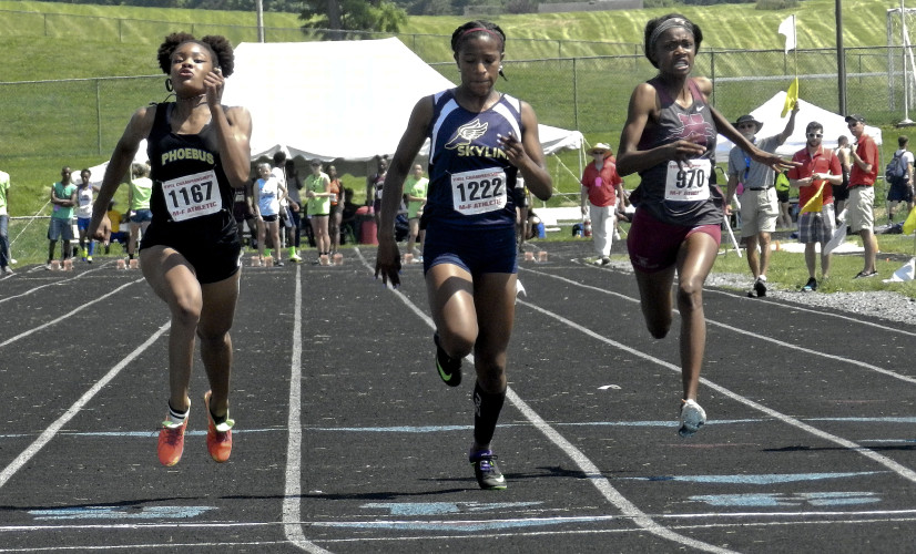 Skyline sophomore Olivia McGill (center) crosses the finish line just behind Phoebus' Amira Aduba in the girls 100-meter dash during Saturday's Group 3A track and field state championships in Harrisonburg. McGill was second in the race.   Brad Fauber/Daily