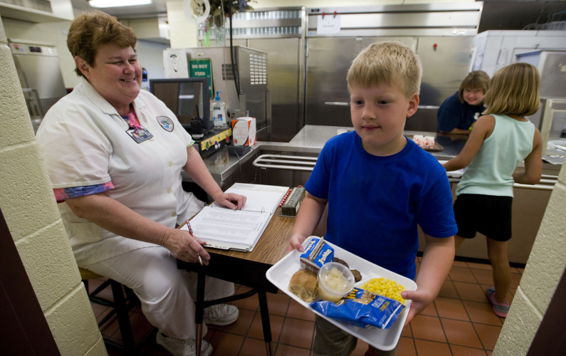 Evan Martz, 6, of New Market, exits the food service line at Ashby Lee Elementary School as Robbin Lawrence, food service manager for the school, records his exit during a recent evening meal at the school.  The hot evening meal is open to all students ages 5 to 18 three days a week at the school. Rich Cooley/Daily