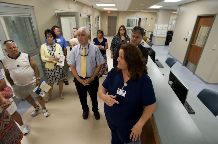 April McClain, director of inpatient nursing and the emergency department, gives the public a tour along the doctors' and nurses' station inside the new emergency room at Shenandoah Memorial Hospital in Woodstock on Wednesday. The new ER  includes 17 private exam/treatment rooms and dedicated trauma and cardiac care rooms.  Rich Cooley/Daily