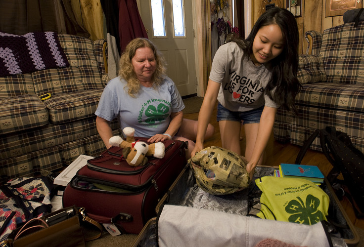 Teresa Funkhouser, left, looks on as Karin Miyamoto,  a 4-H foreign exchange student from Japan, packs her bags for her return home on Saturday. Miyamoto attended Strasburg High School and lived with the Funkhouser family in Toms Brook the past year.  Rich Cooley/Daily