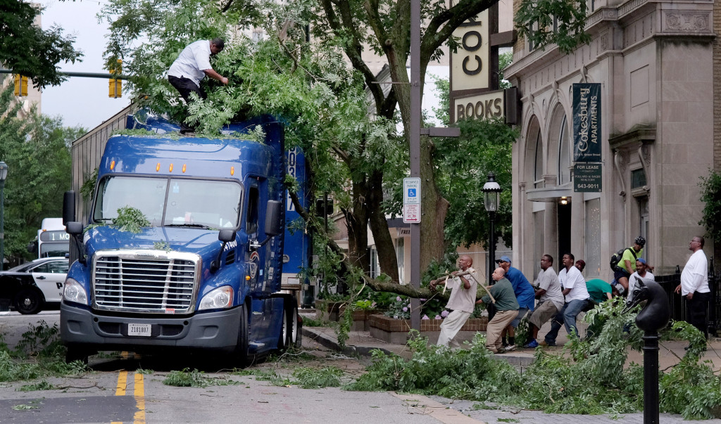 A group of volunteers, right, help a truck driver, standing on top of truck, left, move a large tree limb that had become wedged between the tractor and the trailer of his truck in downtown Richmond, on Friday after a storm the night before downed trees and cut power to thousands in the area. (Bob Brown /Richmond Times-Dispatch via AP)