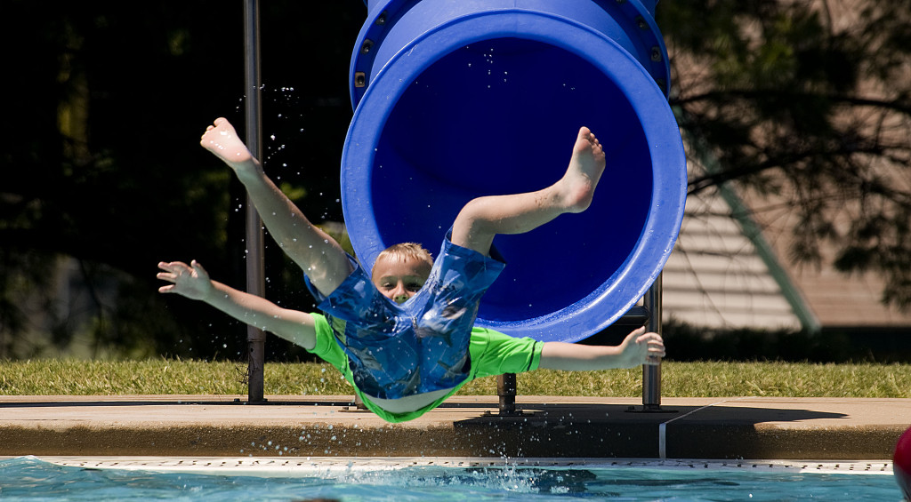 Linkyn Bosworth, 7, of Strasburg, slips out of the water slide at the Claude A. Stokes Community Pool in Bing Crosby Park on a hot Monday afternoon in Front Royal. Monday marked the first day of summer. Rich Cooley/Daily