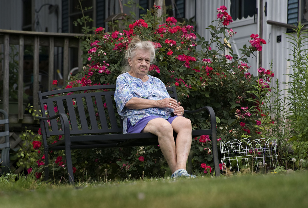 Estella Taylor, 84, of Toms Brook,  watches traffic pass along U.S. Route. 11 as she sits outside with a cold drink by her flowering rose on a summer afternoon.   Rich Cooley/Daily
