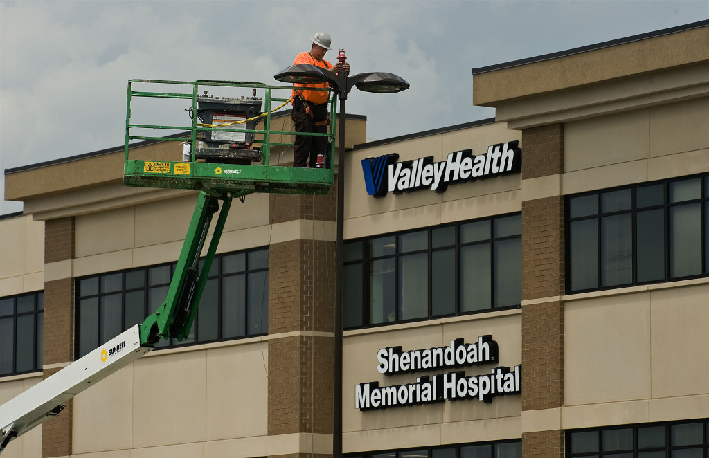 Bradley Link, an electrical supervisor for RCD Electric Inc, of Purcellville, installs red lights for Shenandoah Memorial Hospital's helipad outside the hospital parking lot. The hospital's new emergency room is scheduled to open on Tuesday. Rich Cooley/Daily