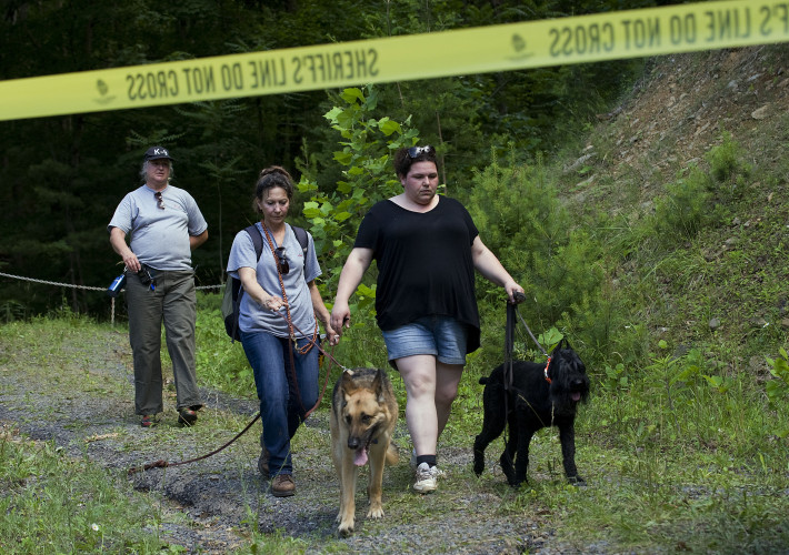 "Martinsburg, West Virginia, EVAK K9 team member Elaine Merceruio, left, and dog handlers Laurie Webber, center, with her German shepherd Lexi, and Erin Compher, with her giant schnauzer Raven, walk back to U.S. Route 50 on Wednesday after the cadaver dogs worked the area where Peggy ""Peg"" Sinclair's body was found on Tuesday. The volunteer team was looking for remains of the victim east of Romney, West Virginia.  Rich Cooley/Daily"